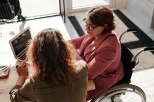 Frau im Rollstuhl sitzt am Tisch vor Laptop
