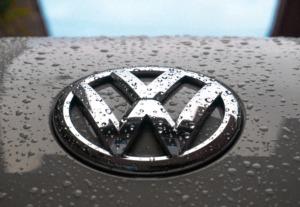 Großes VW-Logo auf dunkler Motorhaube mit Regentropfen übersäht