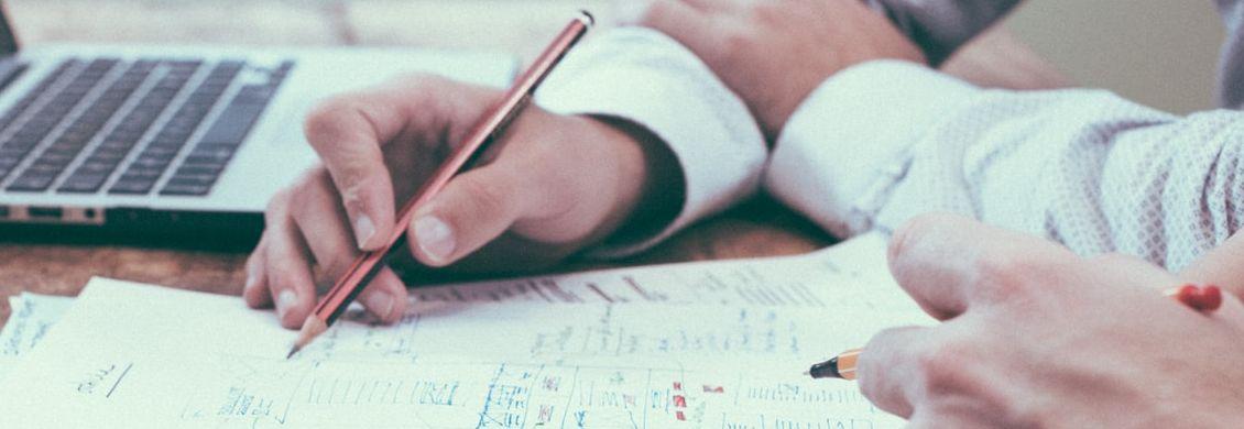 Zwei Hände, die Stifte halten und Notizen auf Zetteln machen
